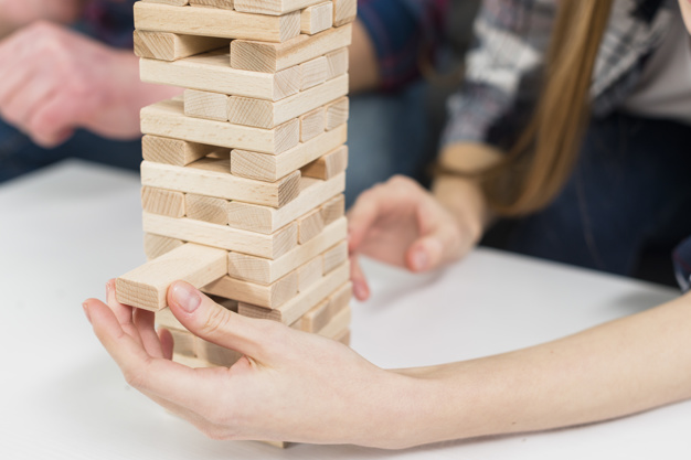 close-up-woman-carefully-removes-block-from-jumbling-wood-tower_23-2148049576